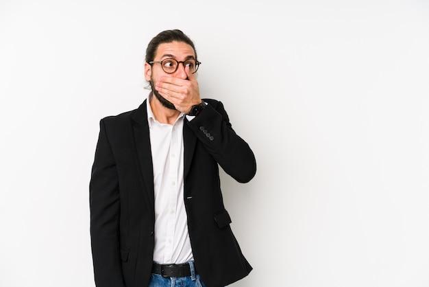 Jeune homme d'affaires isolé sur un mur blanc réfléchi à la recherche d'un espace copie couvrant la bouche avec la main