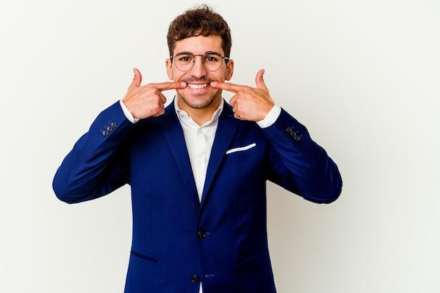 Jeune homme d'affaires isolé sur des sourires de mur blanc, pointant du doigt la bouche
