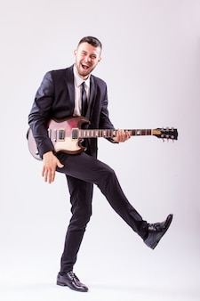 Jeune homme d'affaires jouant de la guitare isolé sur mur blanc