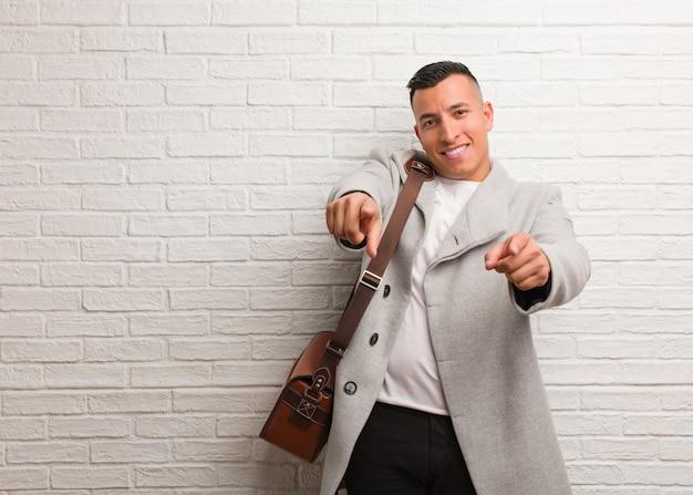 Jeune homme d'affaires latin gai et souriant pointant vers l'avant