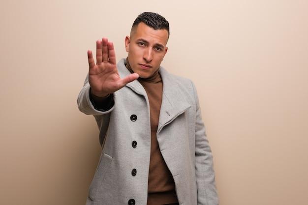 Jeune homme d'affaires latin mettant la main devant