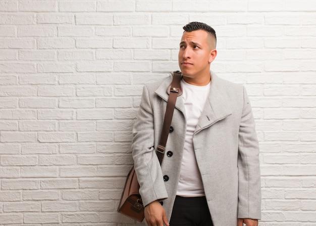 Jeune homme d'affaires latin pense à une idée