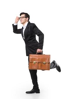 Jeune homme d'affaires à lunettes et costume noir tient une mallette en cuir marron à la main et regarde au loin, isolé sur blanc