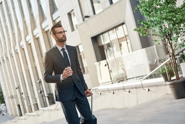 Un jeune homme d'affaires à lunettes monte les escaliers avec du café et une valise