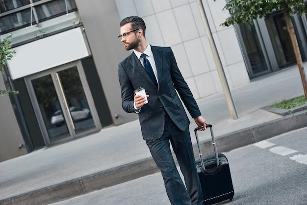 Un jeune homme d'affaires à lunettes traverse la route avec du café et une valise