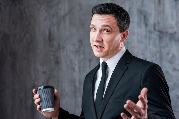 Jeune homme d'affaires avec les mains écartées et tasse à café en regardant la caméra