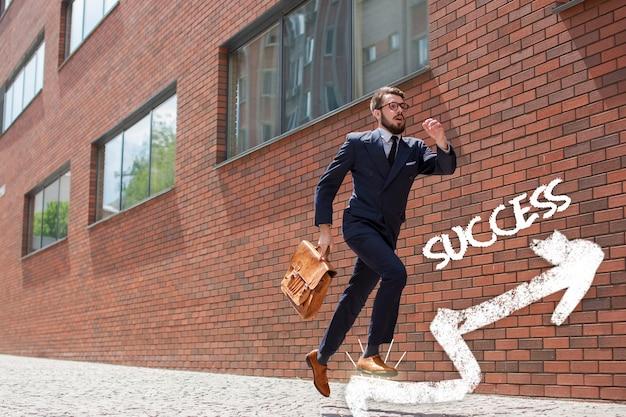 Jeune homme d'affaires avec une mallette et des lunettes courant dans une rue de la ville sur une surface de mur de briques rouges