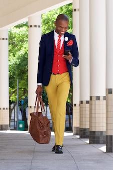 Jeune homme d'affaires marchant et lecture de sms sur téléphone portable