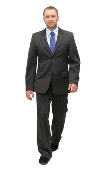 Le jeune homme d'affaires marche. il sourit et regarde la caméra. isolé sur fond blanc