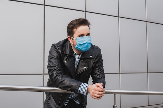Jeune homme d'affaires en masque sur fond d'immeuble de bureaux fermés, coronavirus, maladie, infection, quarantaine, masque médical