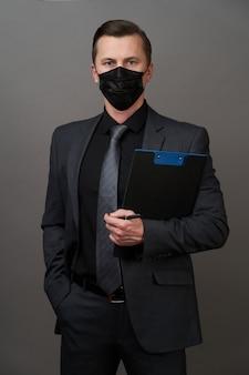 Jeune homme d'affaires avec masque médical chirurgical