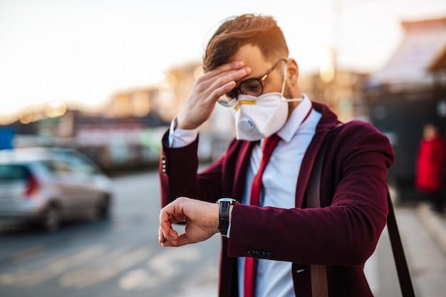 Jeune homme d'affaires avec masque de protection debout seul dans une rue vide et attendant un bus ou un taxi. concept de pandémie de virus ou de pollution.