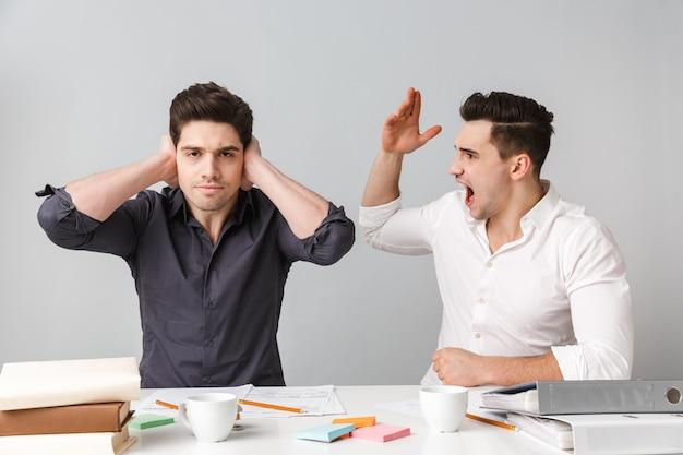 Jeune homme d'affaires mécontent couvrant les oreilles à cause de son collègue