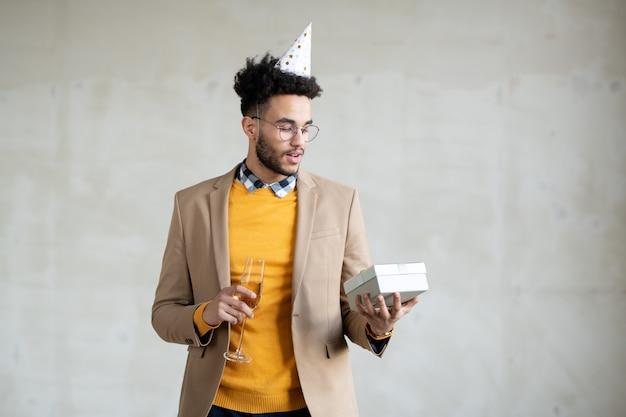 Jeune homme d'affaires métis en tenue décontractée et casquette d'anniversaire tenant une flûte de champagne pétillant tout en regardant une boîte-cadeau dans sa main