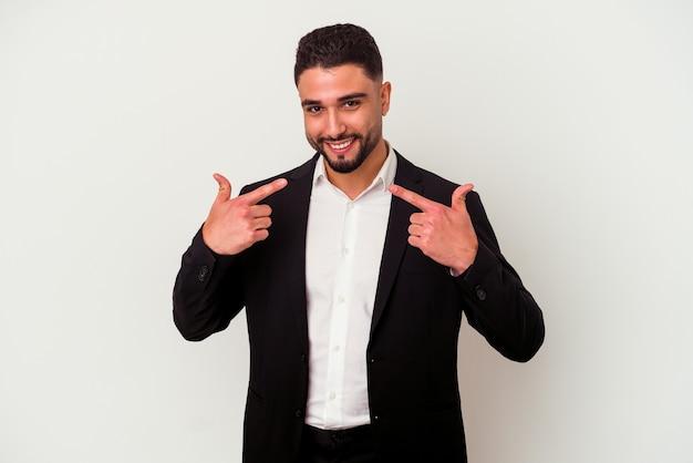 Jeune homme d'affaires métisse isolé sur fond blanc sourit, pointant du doigt la bouche.