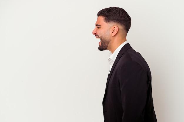 Jeune homme d'affaires métisse isolé sur un mur blanc en criant vers un espace de copie
