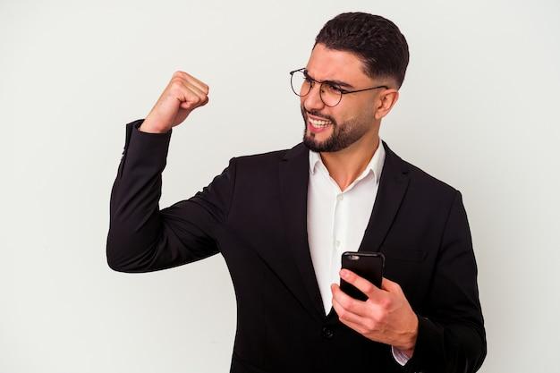 Jeune homme d'affaires métisse tenant un homme de téléphone portable isolé sur fond blanc levant le poing après une victoire, concept gagnant.