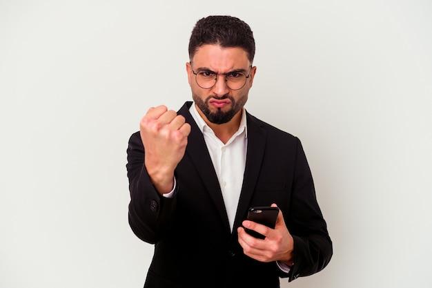 Jeune homme d'affaires métisse tenant un homme de téléphone portable isolé sur un mur blanc montrant le poing à la caméra, expression faciale agressive.
