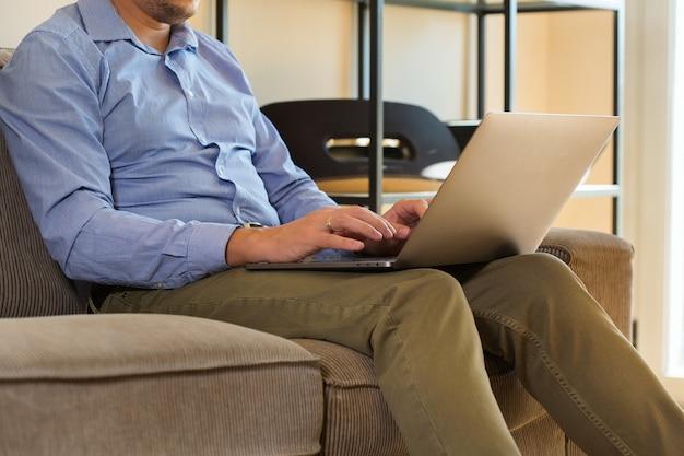 Jeune homme d'affaires millénaire, pigiste travaillant sur un ordinateur portable assis sur le canapé. composition de style de vie avec lumière naturelle. concept de séjour à la maison