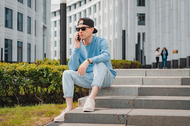 Jeune homme d'affaires de mode attrayant smartphone fond métropole centre d'affaires blanc lecture ...