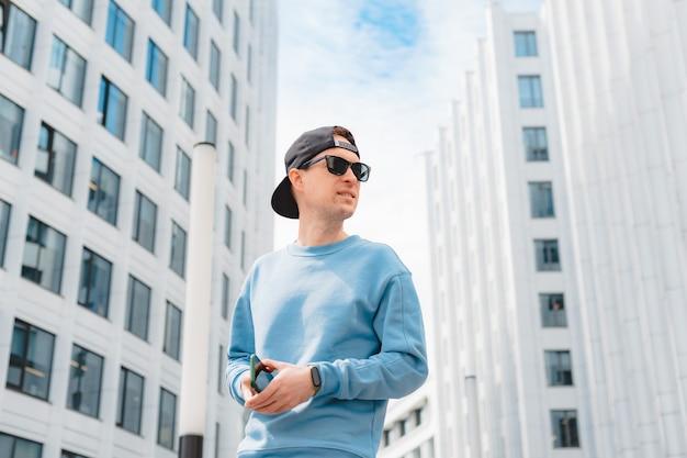 Jeune homme d'affaires de mode avec smartphone au centre d'affaires