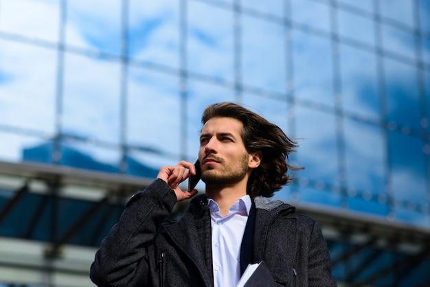 Jeune homme d'affaires moderne confiant debout à l'extérieur avec paysage urbain en arrière-plan