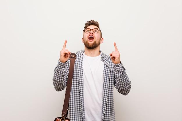 Jeune homme d'affaires moderne pointant à l'envers avec la bouche ouverte.