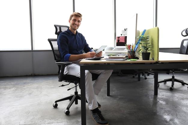 Jeune homme d'affaires moderne travaillant à l'aide d'une tablette numérique alors qu'il était assis au bureau.