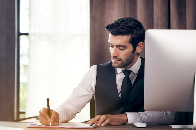 Jeune homme d'affaires moderne travaillant assis au bureau