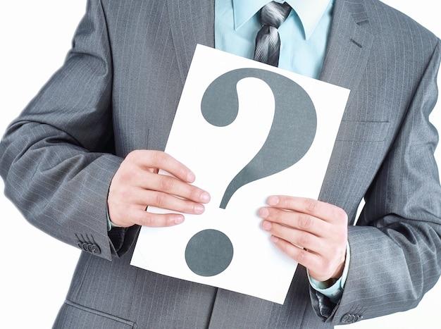 Jeune homme d'affaires montrant une feuille avec un caractère de point d'interrogation.isolé sur blanc