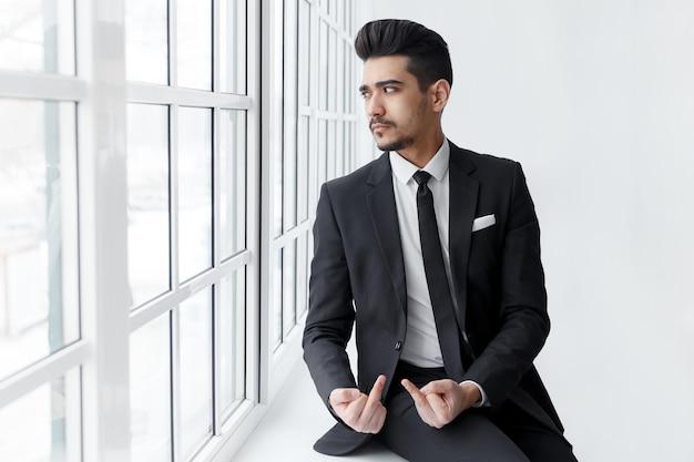 Un jeune homme d'affaires montre un signe de baise