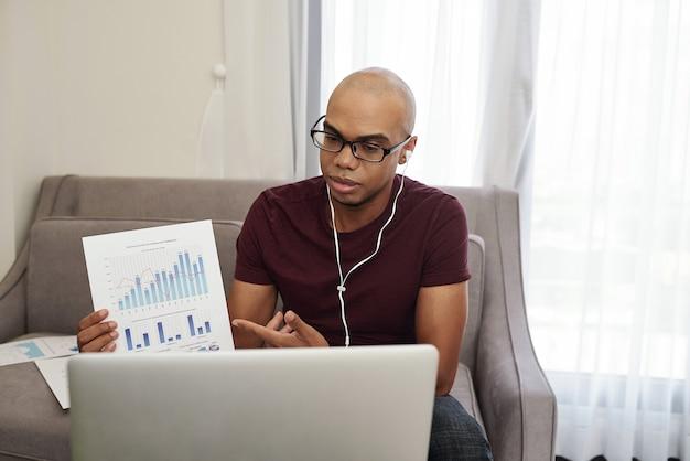 Jeune homme d'affaires noir dans les écouteurs participant à une conférence en ligne et montrant le rapport financier