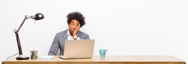 Jeune homme d'affaires noir, ennuyé, frustré et somnolent après une tâche fastidieuse, ennuyeuse et fastidieuse, tenant son visage avec la main sur un bureau