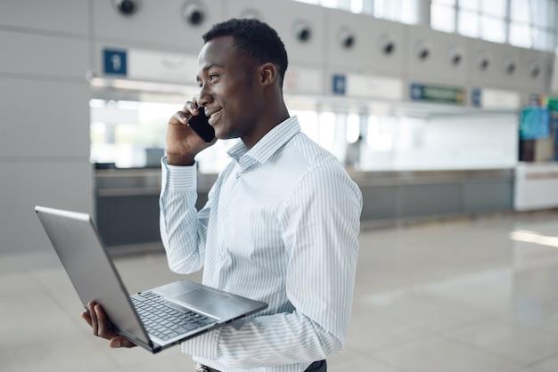 Jeune homme d'affaires noir avec ordinateur portable et téléphone négocie dans la salle d'exposition de voiture. homme d'affaires prospère au salon de l'automobile, homme noir en tenue de soirée