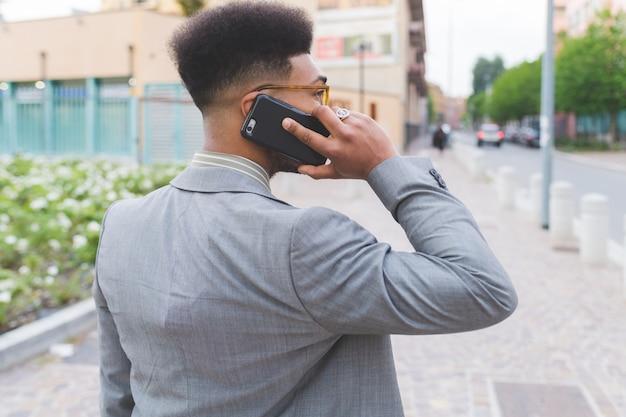 Jeune homme d'affaires noir en plein air parlant de téléphone intelligent