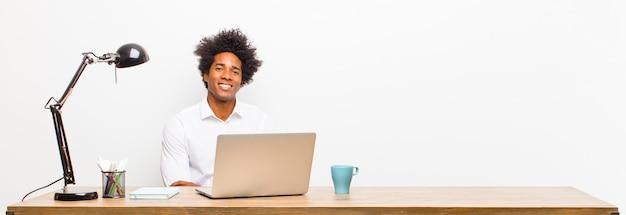 Jeune homme d'affaires noir qui rit timidement et joyeusement, avec une attitude amicale et positive mais incertaine sur un bureau