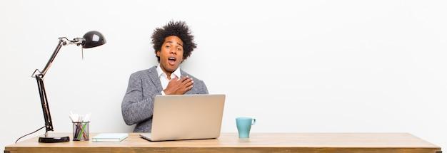 Jeune homme d'affaires noir se sentant choqué et surpris, souriant, prenant la main à coeur, heureux d'être celui ou montrant de la gratitude sur un bureau