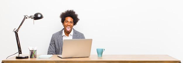 Jeune homme d'affaires noir se sentant dégoûté et irrité, tire la langue, détestant quelque chose de méchant et dégueulasse sur un bureau