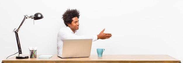 Jeune homme d'affaires noir souriant, vous saluant et offrant une poignée de main pour conclure un accord fructueux, coopération sur un bureau