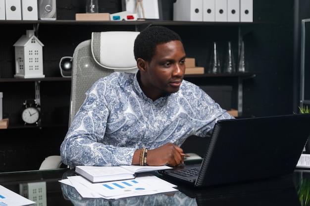Jeune homme d'affaires noir travaillant avec des documents et un ordinateur portable au bureau