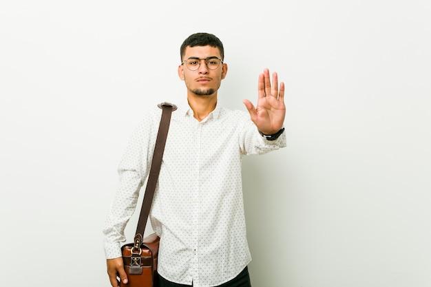 Jeune homme d'affaires occasionnel hispanique debout avec la main tendue montrant le panneau d'arrêt, vous empêchant.