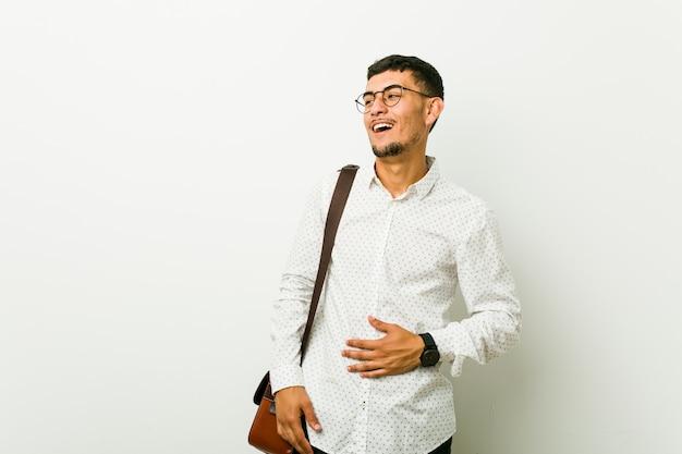 Jeune homme d'affaires occasionnel hispanique touche le ventre, sourit doucement