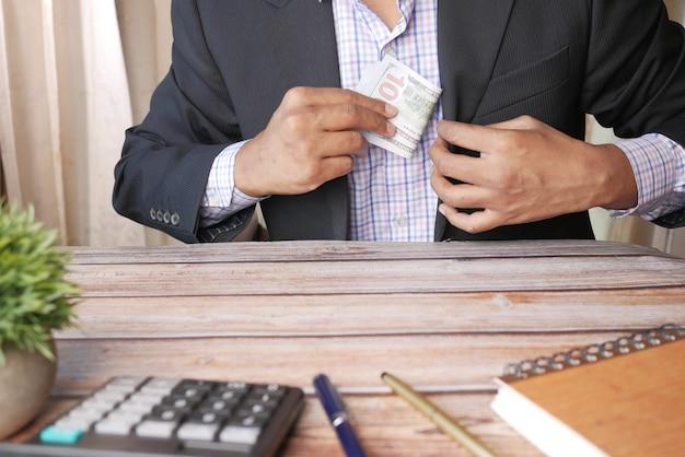 Jeune homme d'affaires offrant de l'argent tout en étant assis sur le bureau