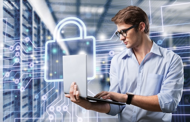 Jeune homme d'affaires avec un ordinateur portable en aluminium moderne et mince dans la salle des serveurs du réseau