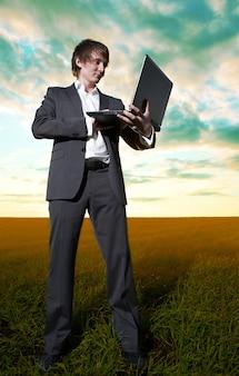 Jeune homme d'affaires avec ordinateur portable dans le champ