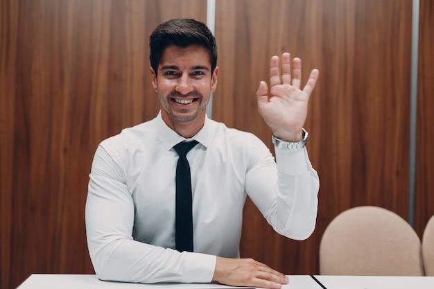 Jeune homme d'affaires avec ordinateur portable à table au bureau en regardant la caméra et en agitant les mains. discussion de réunion de webcam d'appel de conférence vidéo.