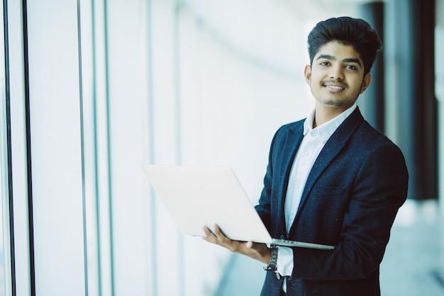 Jeune homme d'affaires avec ordinateur portable travaillant au bureau