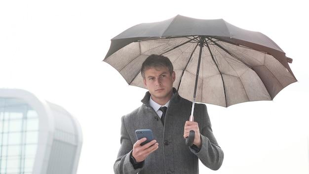 Jeune homme d'affaires avec parapluie et à l'aide d'un téléphone intelligent dans un jour de pluie.