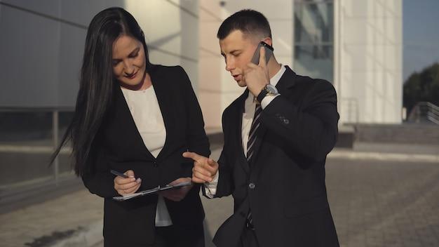 Jeune homme d'affaires parlant sur smartphone debout à côté de son assistant attrayant avec des papiers et un stylo à l'extérieur sur fond de centre d'affaires