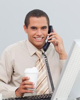 Jeune homme d'affaires, parler au téléphone dans le bureau
